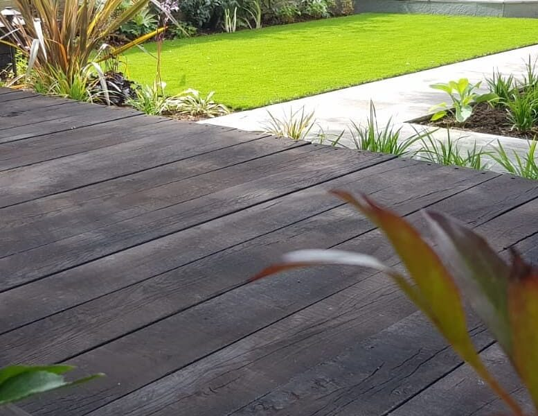 stylish gardens in surrye with decking, lawn and planting