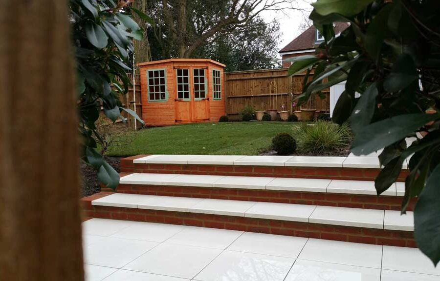back garden with porcelain paving in the foreground with a lawn and summerhouse in the background