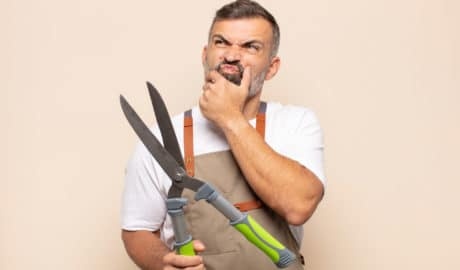 gardener with shears wondering what features to put in his garden