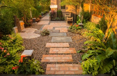 garden worthy of Chelsea flower show with brick paving, gravel and exotic planting